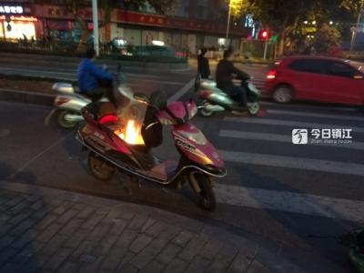镇江大西路电瓶车行驶中自燃,路边摊上半锅水解除险情
