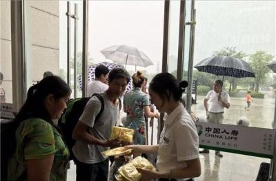 温馨!旅客出站突遇大雨,车站发放免费雨衣