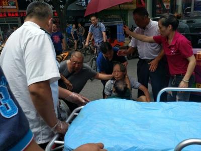 老人被车撞倒,热心市民高温下撑伞守护