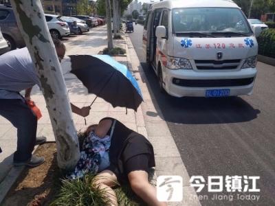 烈日下女子骑车摔倒昏迷 热心市民撑伞为其遮阳