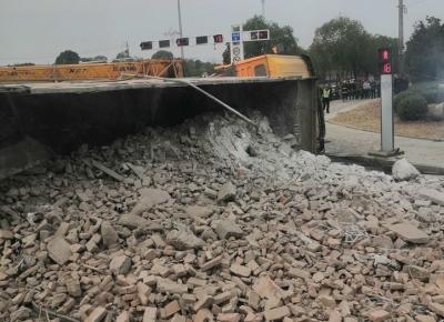 金港大道上渣土车压扁小轿车 事故造成两车受损 轿车上两人一死一伤