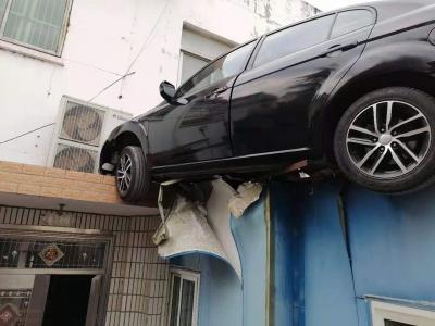 司机驾车分神  轿车飞上屋顶